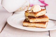 在一块圆的板材和奶油的片断砂锅,倒蜂蜜 免版税库存照片