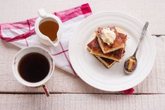 在一块圆的板材和奶油,杯子咖啡的片断砂锅,倒蜂蜜 图库摄影