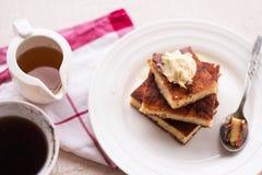 在一块圆的板材和奶油,杯子咖啡的片断砂锅,倒蜂蜜 免版税库存照片