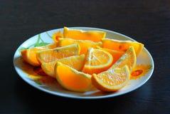 在一块圆的板材的水多的明亮的橙色切片 免版税库存照片