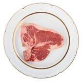 在一块土气板材的未加工的丁骨牛排,被隔绝 免版税库存图片