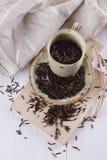 在一块土气陶瓷板材的黑水菰在白色木背景 库存照片