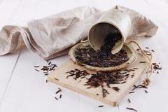 在一块土气陶瓷板材的黑水菰在白色木背景 免版税库存照片