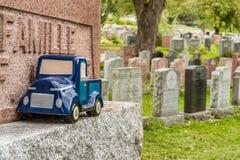 在一块墓碑的蓝色汽车玩具在公墓,象征死亡 库存图片