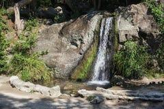 在一块大石头的装饰瀑布 库存照片