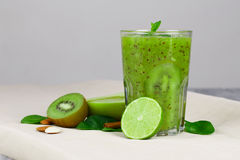 在一块大透明玻璃的鲜绿色的圆滑的人鸡尾酒 猕猴桃饮料用在灰色的新伐绿色果子 免版税库存照片