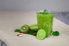 在一块大透明玻璃的鲜绿色的圆滑的人鸡尾酒 猕猴桃饮料用在灰色的新伐绿色果子 库存照片