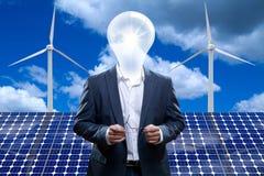 在一块太阳电池板前面的富创意的人。 图库摄影