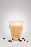 在一块小玻璃的热奶咖啡用咖啡豆 免版税库存图片