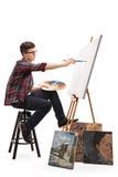 在一块帆布的少年画家绘画与油漆刷 库存图片