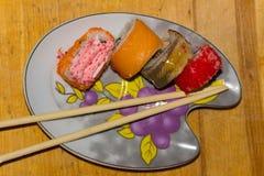 在一块形象的板材的寿司卷在木背景 免版税库存图片