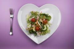 在一块心形的板材和叉子的传统沙拉 免版税图库摄影