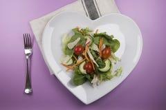 在一块心形的板材和叉子的传统沙拉 免版税库存照片