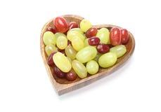 在一块心形的板材的葡萄 免版税库存照片