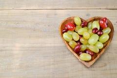 在一块心形的板材的葡萄 库存图片