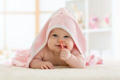 在一块戴头巾毛巾下的可爱宝贝咬住的teether在浴以后 库存照片