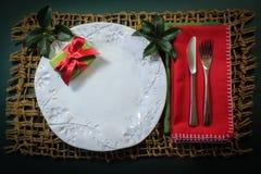 在一块手工制造板材的圣诞节礼物有霍莉小树枝的和在一张重的被编织的席子的红色餐巾 免版税库存图片