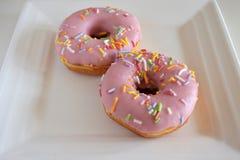 在一块方形的白色板材服务的两个甜桃红色油炸圈饼 图库摄影