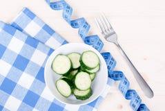 在一块方格的餐巾的黄瓜沙拉在厘米和叉子旁边, 库存图片