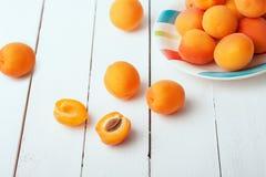 在一块明亮的板材的可口成熟橙色杏子在白色木桌特写镜头 水平的看法从上面 库存图片