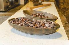 在一块木板材的干有机可可粉巧克力种子 免版税图库摄影