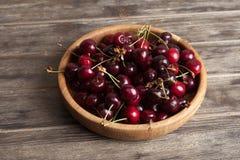 在一块木板材的新鲜的樱桃在老木背景 新收获从事园艺 烹调和素食食物的成份 免版税库存图片