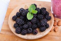 在一块木板材的甜黑莓在白色背景 未加工和成熟莓果用薄菏和圆滑的人在书桌上 库存照片