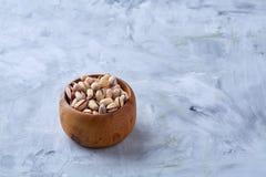 在一块木板材的盐味的开心果在白色背景,顶视图,特写镜头,选择聚焦 免版税库存图片