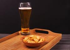 在一块木板材的薄脆饼干有一杯的在一张木桌上的啤酒 免版税库存照片