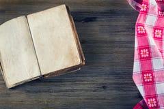 在一块木桌和宽松地被放置的厨房餐巾上的老开放书 免版税库存照片
