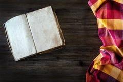 在一块木桌和宽松地被放置的厨房餐巾上的老开放书 免版税图库摄影