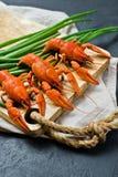 在一块木砧板的煮熟的红河小龙虾 黑背景,顶视图 库存照片
