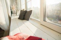 在一块木窗口基石的布朗坐垫 免版税库存图片
