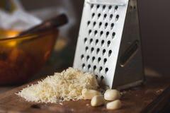 在一块木面包板的一些cheeseand大蒜 磨丝器 图库摄影