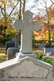 在一块未玷污的花岗岩墓石上面的一个石十字架在断头谷公墓,在安静和安静的秋天下午 库存照片