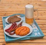在一块板材和玻璃的烤香肠用低度黄啤酒 库存照片