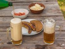 在一块板材和玻璃的烤香肠用低度黄啤酒 免版税库存图片