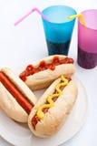 在一块板材的三个热狗有饮料的 免版税图库摄影