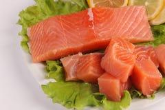 在一块板材的三文鱼用沙拉和柠檬 库存照片