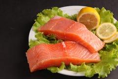 在一块板材的三文鱼用沙拉和柠檬 图库摄影