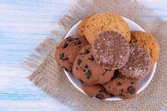 在一块板材的不同的曲奇饼在与餐巾的一张蓝色木桌上 bacterias 美味 在视图之上 库存图片