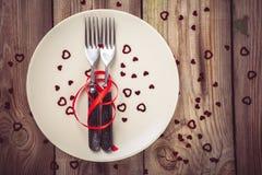 在一块板材的两把叉子有一条红色丝带的 免版税库存图片