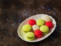 在一块板材的五颜六色的macarons在黑暗的背景 Macaron或蛋白杏仁饼干是与拷贝空间的甜基于蛋白甜饼的混合药剂 免版税图库摄影