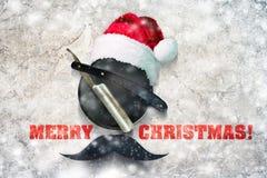 在一块板材的剃刀与一个圣诞老人项目帽子的泡沫的在灰色背景 题字圣诞快乐 愉快的贺卡 免版税库存图片