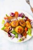 在一块板材的加香料的被烘烤的嫩土豆土豆用菜沙拉与 免版税库存照片