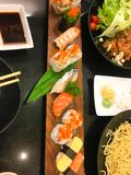 在一块板材的寿司卷有三文鱼的,金枪鱼,皇家大虾,乳脂干酪 寿司菜单 日本食物 加利福尼亚寿司,日本餐馆人 库存图片