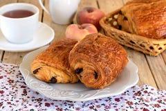在一块板材的巧克力新月形面包用茶早餐 库存图片