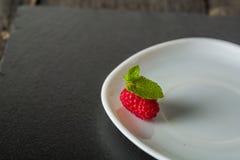 在一块板材的成熟水多的莓在黑暗的背景 新绿色留下薄菏 图库摄影
