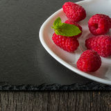 在一块板材的成熟水多的莓在黑暗的背景 新绿色留下薄菏 免版税库存图片
