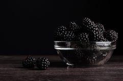 在一块板材的新鲜的成熟水多的黑莓在黑背景 库存图片